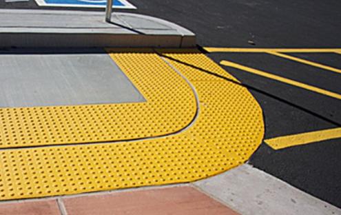 С целью облегчить передвижение для инвалидов и людей с плохим зрением была разработана тактильная плитка для пешеходных дорожек. Используемый при ее изготовлении материал тактил имеет некоторые свойства. Например, его можно использовать в качестве дорожных указателей или в виде информатора для маршрутов. В нынешнее время тактил активно используется в городах, при оформлении парковых и других ландшафтных зон, а также внутри больших объектов с высокой посещаемостью людей. Указатели из тактила инвалидам по зрению помогают осваиваться в окружающей среде, выбирать нужное направление своего перемещения, повышать его безопасность. Важным моментом является тот факт, что тактильное покрытие для пешеходных дорожек бывает не с гладкой поверхностью, что обеспечивает прекрасный противоскользящий эффект. Плитка такого вида достаточно безопасна для людей, имеющих проблемы со зрением, в любых погодных условиях. Покрытие из тактила устойчиво к влажной среде, химическому воздействию. Благодаря своей прочной структуре покрытие из тактила может устанавливаться в местах, с высокой степенью эксплуатации. В течение длительного периода времени тактильное покрытие не поддается воздействию солнечного света и не меняет свой цвет, даже наоборот - сохраняет свой замечательный внешний вид. Для чего нужна тактильная плитка Сейчас в России разработаны и введены в действие несколько программ, направленных для улучшения социальной интеграции инвалидов. Например, программа «Год равных возможностей». Государство наконец-то начало поворачиваться лицом к людям с ограниченными возможностями и их проблемам. Практически все общественные места начали оборудовать пандусами, в целях облегчить передвижение по лестницам людям на инвалидных колясках. Не обошли стороной и слепых людей и с плохим зрением. Специально для этой категории людей в городах монтируются тактильные указатели. Спуститься самостоятельно в подземный переход, перейти проезжую часть дороги, найти нужное место как на открытой местности, так и вн